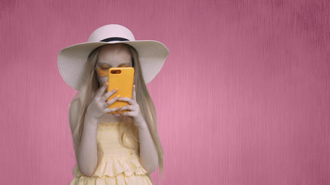 Child girl in summer hat is looking at phone and thinking Footage