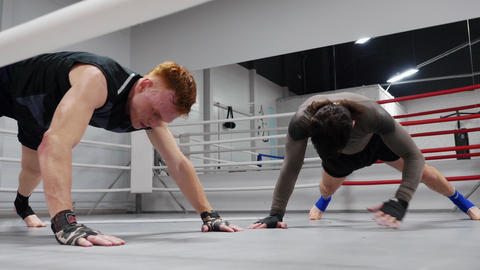 Two fighters are training on ringside make exercises in plank in fight club Footage