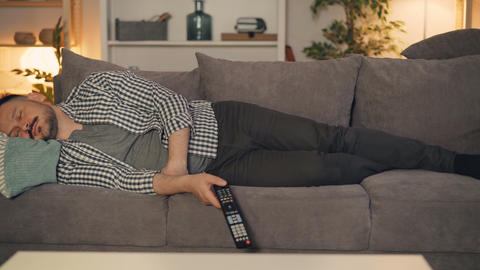 Portrait of tired person sleeping on couch alone holding TV remote control Footage