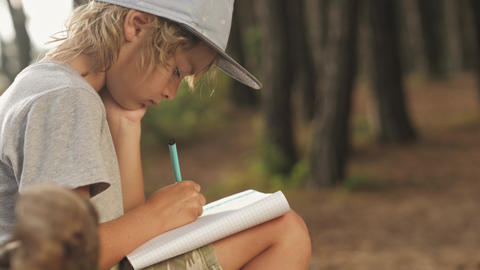 Child makes sketches in notebook on wood background Live Action