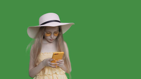 Child girl with long hair is browsing mobile phone on summer vacation alpha Footage