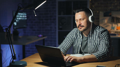 Cheerful man enjoying music in headphones and working with laptop in dark office Footage
