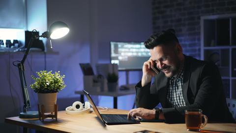 Happy businessman enjoying business telephone conversation in dark office Live Action