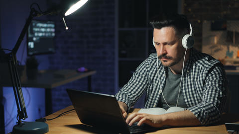 Attractive man finishing work in office turning off laptop and lamp at night Footage