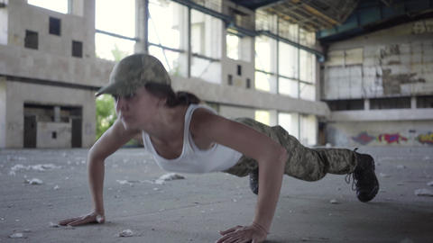 Pretty strong confident young woman in military uniform push-ups in a deserted Footage