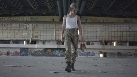 Attractive young woman in military uniform walking slowly in dusty dirty Live Action