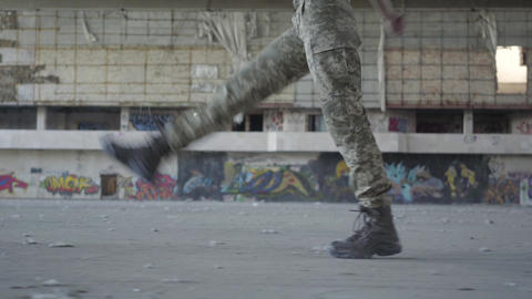 Female legs in military uniform marching on the concrete floor in dusty dirty Live Action