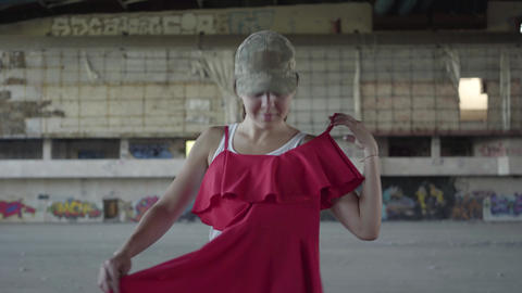 Cute young woman in military uniform trying on red dress and dancing around Footage