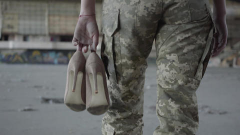 Legs of young woman in military uniform walking slowly in dusty dirty abandoned Live Action