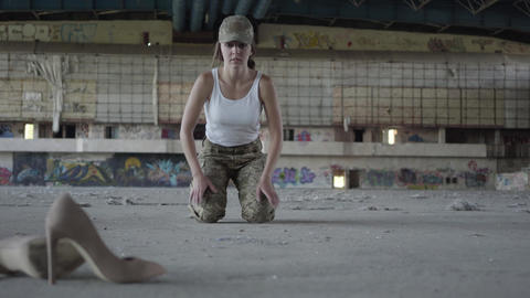 Strong young woman in military uniform wringing herself from the floor on a Live Action