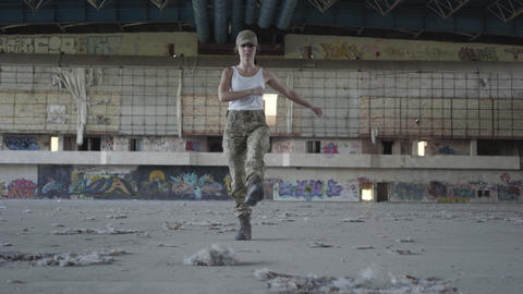 Attractive young woman in military uniform marching on concrete floor in dusty Footage