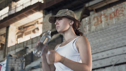 Portrait of attractive young woman in military cap drinking water from the Footage
