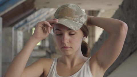 Portrait of attractive young woman putting on military cap on her head and Footage