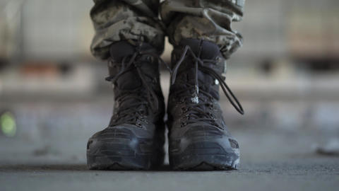 Feet of the soldier in old boots making a step forward on the dusty dirty Live Action
