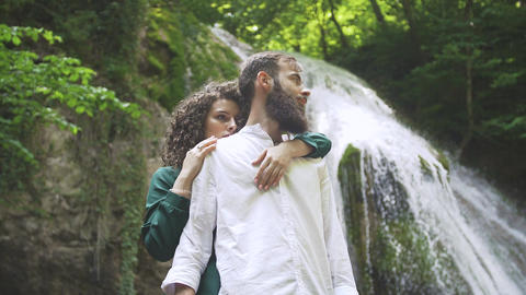 beautiful woman hugging a man with a beard from the back on the background of a Footage