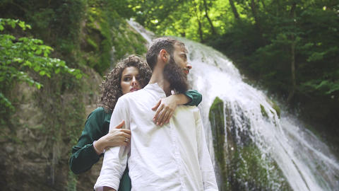 attractive woman hugging a man with a beard from the back on the background of a Footage