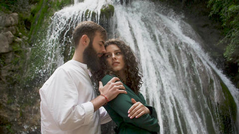 a man with a beard passionately embraces a woman with curly hair from behind Live Action