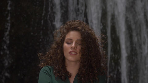 young adorable woman with curly hair smiling against a waterfall Footage