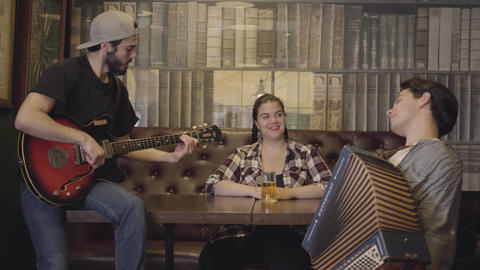 Joyful young smiling bearded man playing guitar in the bar, his friend playing Live Action