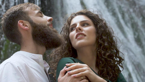 attractive man with a beard hugging a woman with curly hair behind a waterfall Footage