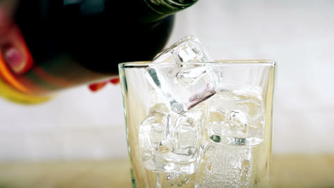 barman pouring whiskey in the glass with ice cubes on wood table background, focus on ice cubes, Live Action