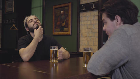 Two men drinking beer sitting at a table in a pub. Guys having fun together Footage