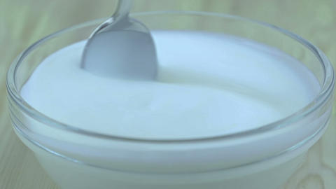 man use the spoon to eat the yogurt in the transparent cup, ready for insert healthy strawberries, Footage
