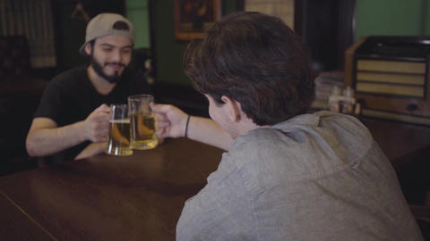 Two guys drink beer clinking glasses while sitting at a table in a pub. Guys Live Action
