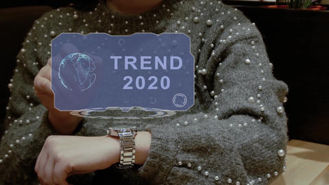Woman uses hologram watch with text Trend 2020 Footage