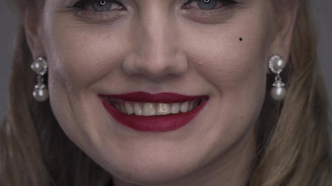 Close up of a young woman with red lipstick blowing a kiss, 4k Live Action