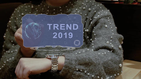 Woman uses hologram watch with text Trend 2019 Live Action