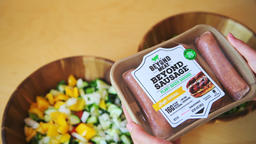Closeup of hands holding raw beyond meat sausages package with salad bowls Footage