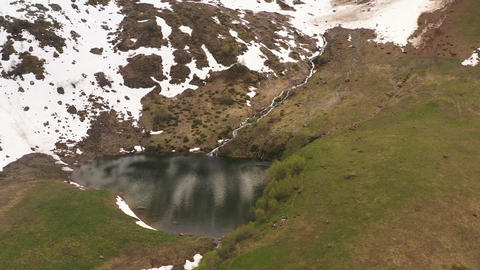 Aerial view from snow covered mountain slope to picturesque mountain lake. Dark water surface heart Live Action