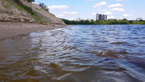 Small waves washing up a river shore with light brown sand in a sunny day Footage