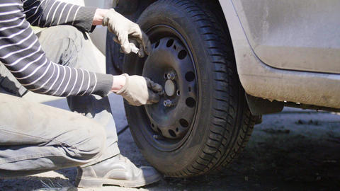 Man car technician replaces tire of car wheel on road in street on sunny day Footage