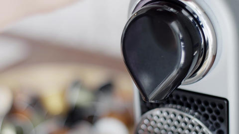 Closeup view of black compact coffee machine spout ready to pour coffee Live Action