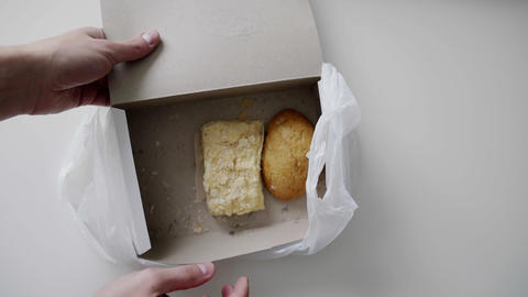 Man's hands takes bun out of white paper box placed in white plastic bag Live Action
