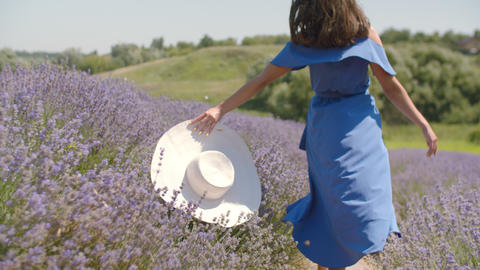 Carefree woman with hat runs through floral glade Footage