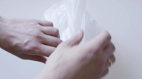 Someone unwraps white cellophane bag covering plastic container with cake in it Footage