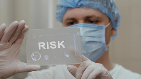 Doctor uses tablet with text Risk Footage