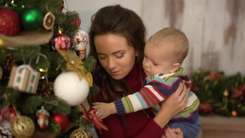 Pretty young woman shakes the baby in her arms standing near christmas tree and Footage