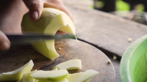 Old lady using knife to peel a winter melon. Ingredient for cooking Live Action