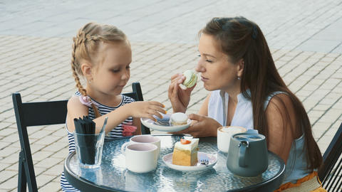 Mother and her cute little daughter in outdoor cafe Footage