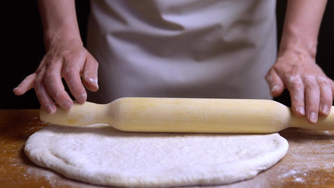 Rolling the dough with a rolling pin on the table. close-up 4K Live Action