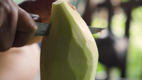 Old lady using knife to cut a winter melon to pieces. Ingredient for cooking Live Action