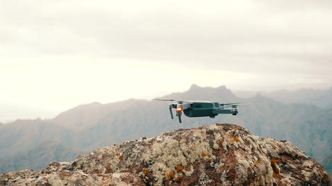 Close up of a consumer drone landing on a rough rock high in Mountains. Slow Live Action