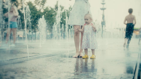 Mother and her little baby having fun in city park fountain, slow motion Footage