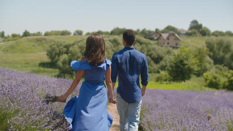 Stylish mixed race couple walking in blooming field Stock Video Footage