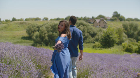Stylish mixed race couple walking in blooming field, Live Action