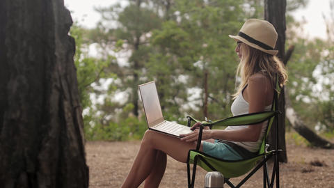 Smiling girl working on laptop outdoors in summer vacation Footage
